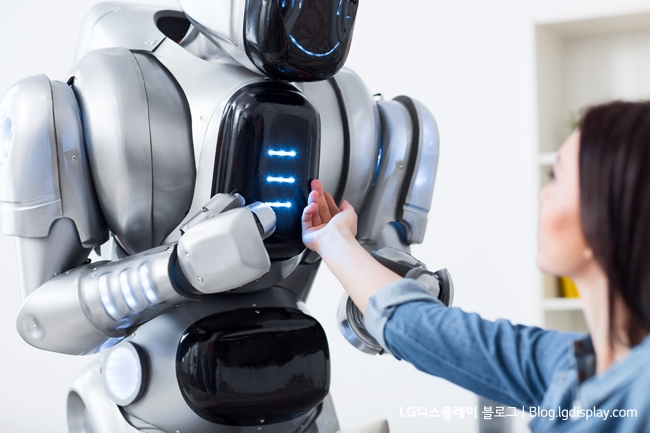 It is beating. Pleasant charming girl holding her hand on the robot and looking at it while having a leisure time
