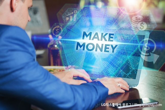 Business, Technology, Internet and networking concept. Young businessman working on his laptop of the future, working with the virtual screen hologram. The inscription on the screen:make money.